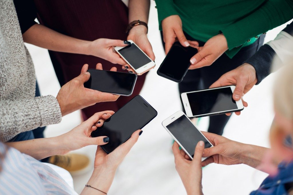 Group of friends using their smartphone