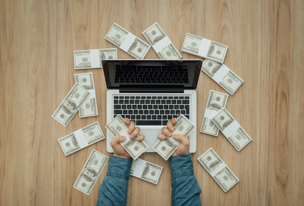 Person holding cash in front of the laptop