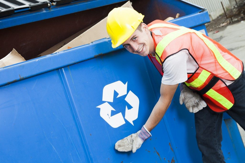 Worker showing a trash container for recycling