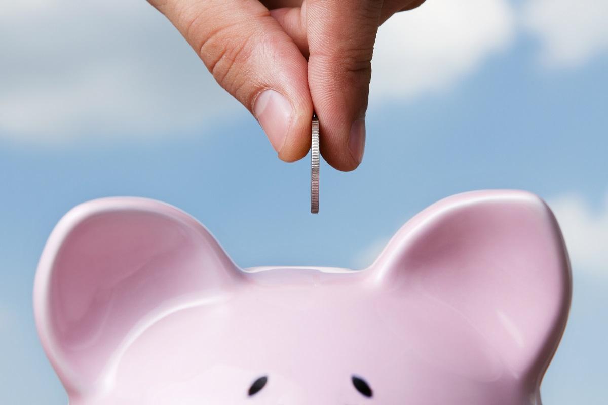 putting coin in piggybank