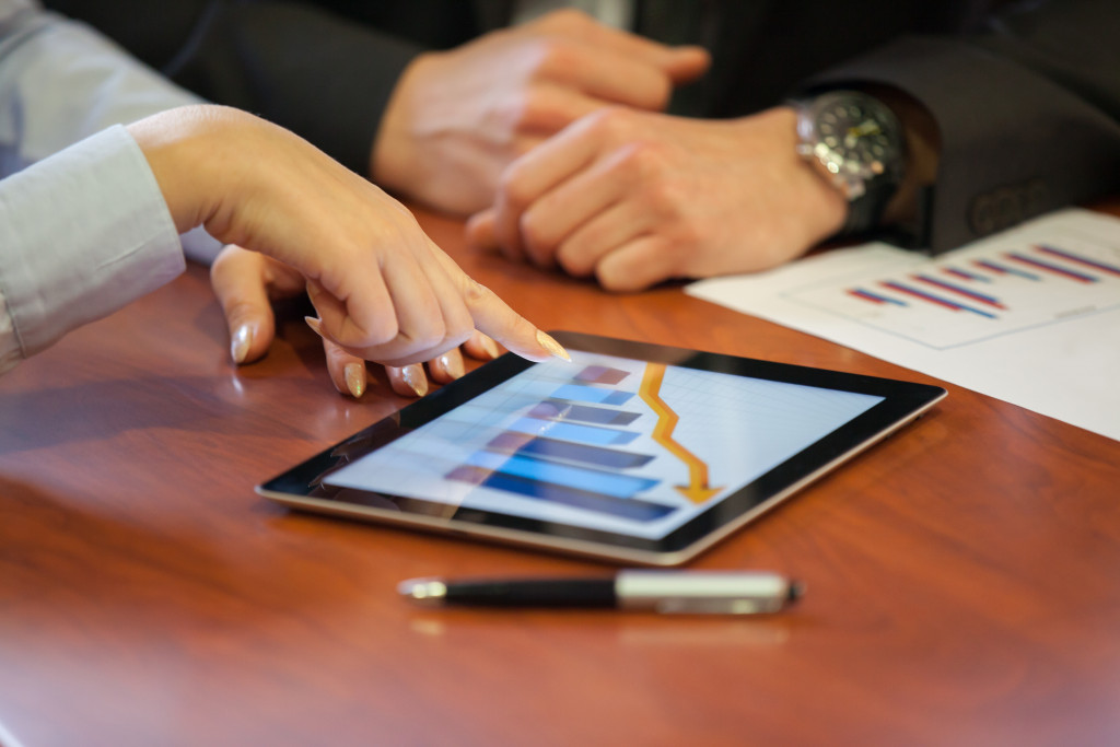 woman pointing on tablet about finance